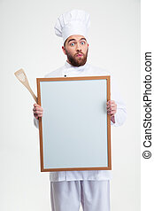 Funny male chef cook holding blank board