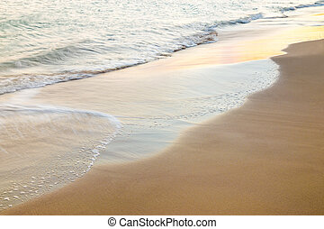 Beautiful wave on a sand beach at sunset