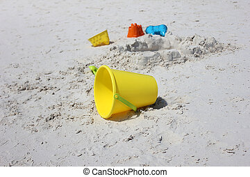 Child's bucket, spade and other toys on tropical beach...