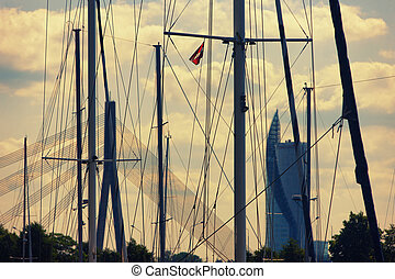 Cable-stayed bridge and skyscrapers through the masts of yachts