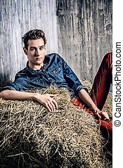 country style - Casual young man lying relaxed on a haystack...