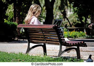 Young woman with laptop on the park - View of a young woman...