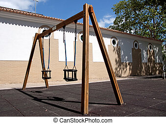 Empty playground swings - View of a public park with a pair...