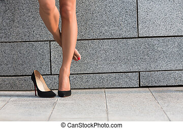 Low view of womans legs - Woman put off right leg from her...