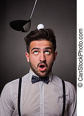 Handsome man with a golf ballon his head in studio -...