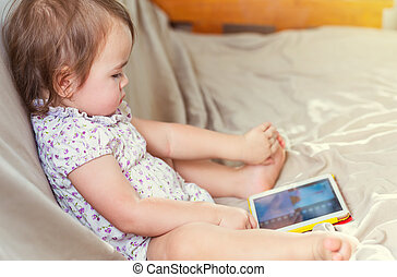 Toddler girl watching watching her tablet - Toddler girl...