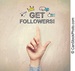 Hand pointing to Get Followers concept on light brown wall...