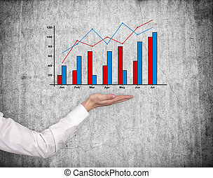 hand holding stock chart on gray wall background