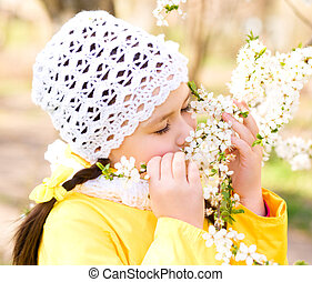 Little girl smelling flowers outdoors