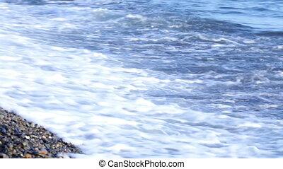 Waves of the sea splash on pebble