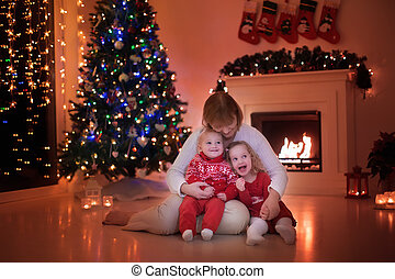 Family at fire place on Christmas - Mother and children read...
