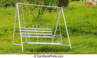 metal swing bench against green grass in tourist park -...