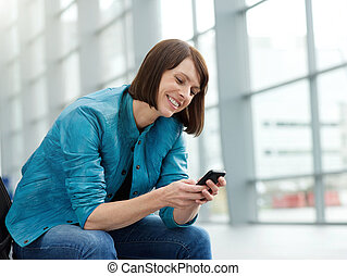 Beautiful older woman smiling with mobile phone