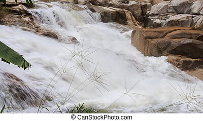 closeup foamy mountain stream flows against stones in park -...
