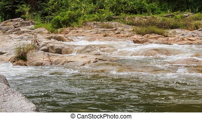 camera approaches mountain stream on plane surface in park -...