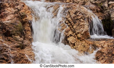 closeup cascade of stormy foamy waterfalls in park - closeup...