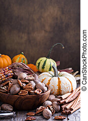 Pumpkins, nuts, indian corn and variety of squash on a...
