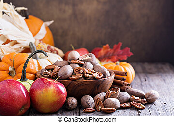 Pumpkins, nuts, indian corn and apples on a rustic table