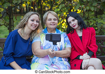 Two daughter with old mother taking selfie by phone with...
