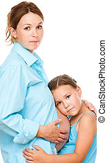 Child holding belly of pregnant woman
