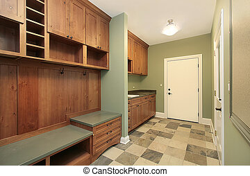 Mud room in luxury home with wood paneling