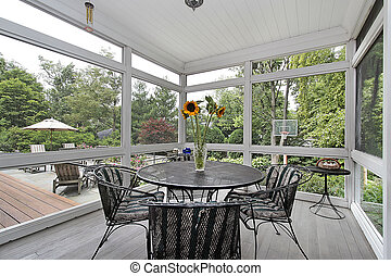 Screened in porch with table and wood floor