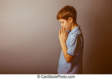 boy European appearance in a blue shirt praying closed his...
