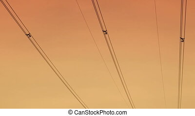 high voltage pylons at sunset. 30 fps