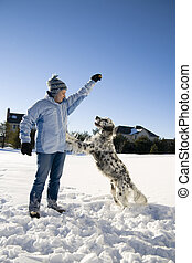 Playing in the snow - Girl playing with the dog in fresh...