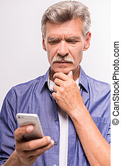 Senior man is using smartphone, standing on white background...