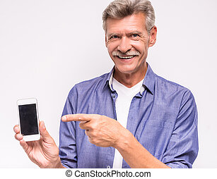 Senior man is using smartphone, standing on white...