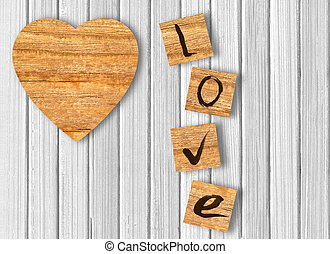 Wood heart on white wooden background. Love cast out of wood...
