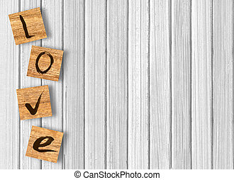 Love cast out of wood kubik on white wooden background