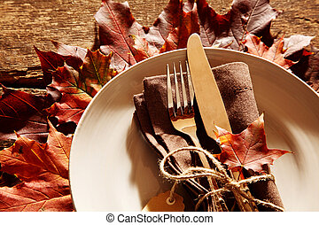 Fall or autumn themed place setting with a knife, fork and...