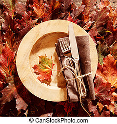 Autumn themed place setting with cutlery and a brown napkin...