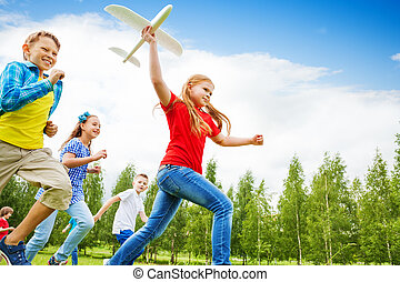 View from below of girl holding big airplane toy - View from...