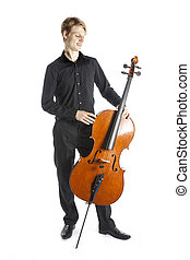young blond caucasian man stands next to cello in studio...