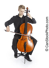 young blond caucasian man plays the cello in studio against...