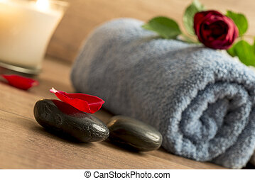 Romantic atmosphere with a red rose on top of rolled towel,...