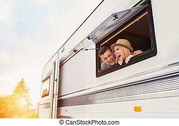 Young couple sitting in a camper van - Beautiful young...
