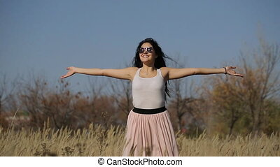 Woman with arms outstretched in a wheat field slow motion