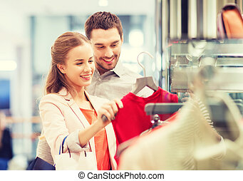 happy young couple choosing dress in mall - sale,...