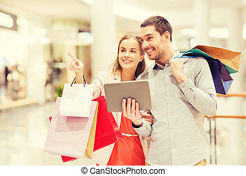 couple with tablet pc and shopping bags in mall - sale,...