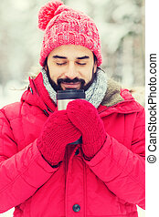 smiling young man with cup in winter forest - season,...
