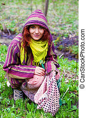 Young girl collects herbs on a glade in ethno clothing