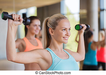 group of women exercising with dumbbells in gym - fitness,...