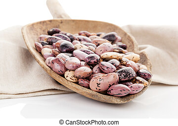 Pinto beans. - Pinto beans on wooden scoop on beige table...