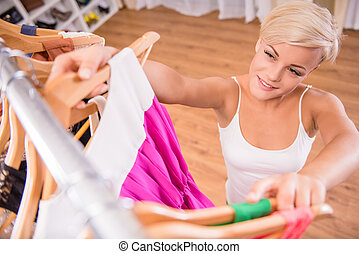 Wardrobe - Top view of young woman in the store is looking...