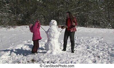 Family Building Snowman In Garden - Two girls wearing gloves...