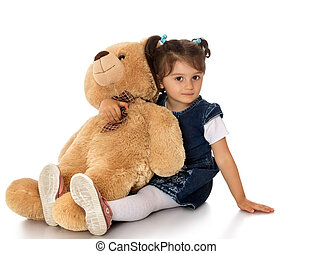 girl with teddy bear - Cute little dark-haired girl sat down...